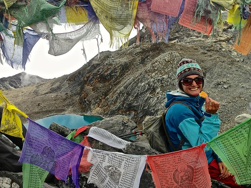 Lina surrounded by prayer flags, enjoying a cookie on Kongma La Pass