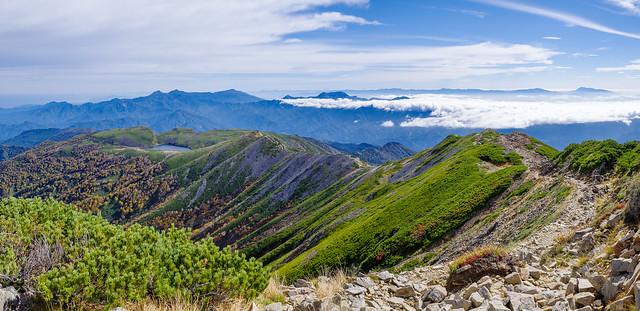 登ってきた稜線の背後には妙高戸隠連峰や遥か日光上信越の山々が連なる