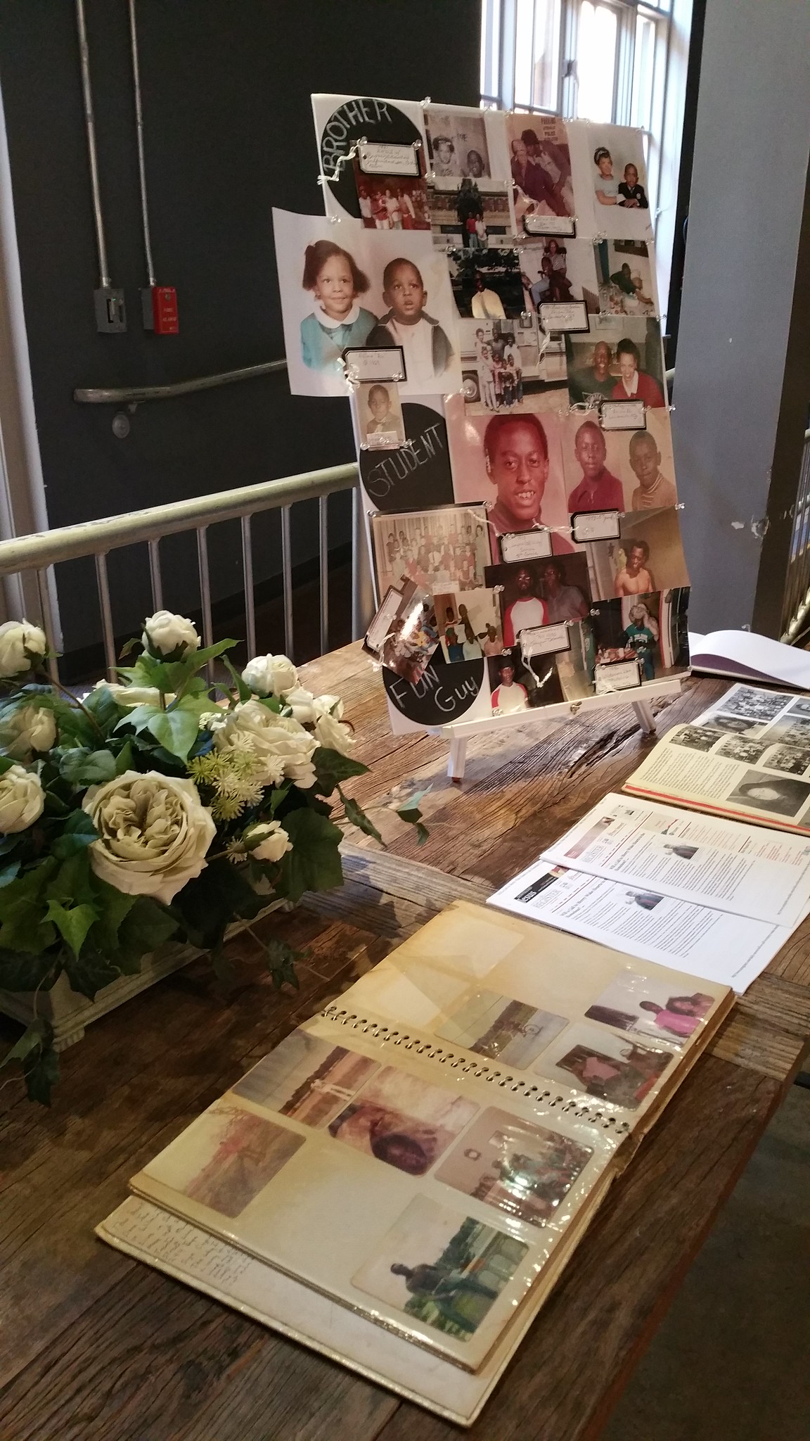 A table with white roses, a family album, and a photo collage on it.