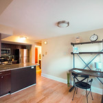The cherry wood in the kitchen compliments the light hardwood floors found throughout the apartment.