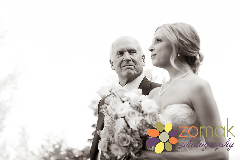 Father of the bride looks at her lovingly as he escorts her down the aisle