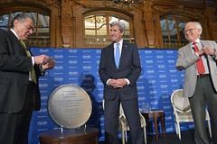 U.S. Secretary of State John Kerry is presented with a plaque from Saban Forum Chairman Haim Saban in his appearance at the The Brooking Institution's 2016 Saban Forum at the Willard Hotel in Washington, D.C. on December 4, 2016. [State Department Photo/Public Domain]