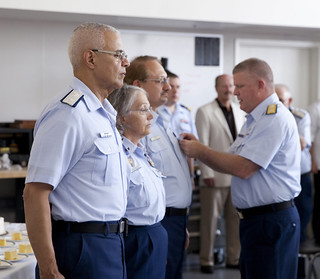 Rear Adm. Fred Midgette pins the Coast Guard Unit Commendation Ribbon on the chest of Coast Guard Auxililarist Edward Monaco, after awarding similar ribbons to Commodores Llorens (Joe) Chenevert and Maureen Van Dinter at a ceremony in the Coast Guard Cleveland Moorings, June 30, 2014. The ceremony marked the 75-year anniversary of the Coast Guard Auxiliary, the all-volunteer support complement to the Coast Guard. U.S. Coast Guard Photo by Auxiliarist Mark Galan