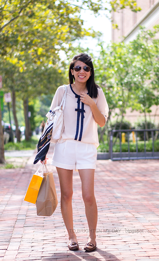 bow blouse, white cuffed shorts, chain scarf, white tote bag, brown loafers