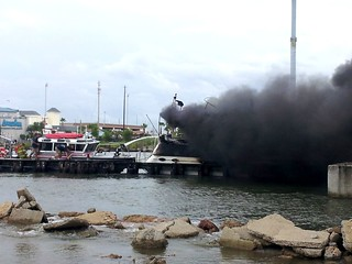 A boat burns under the 146 bridge near Kemah Boardwalk in Kemah, Texas, Friday, Aug. 29, 2014. Three people aboard the boat were able to get off safely, and a good Samaritan reported the fire to the Coast Guard, which initiated the response. (U.S. Coast Guard photo by Sector Houston/Galveston)