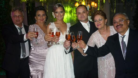 Os noivos Olívia e Leonardo com seus pais brindando a felicidade