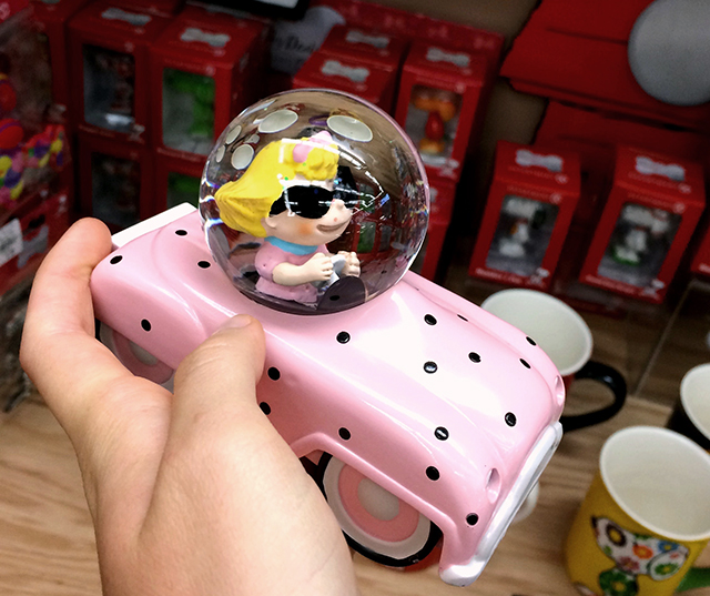 Sally from Peanuts in a pastel pink polka-dot car