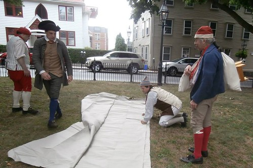 18th century sailors prepare to sew a sail