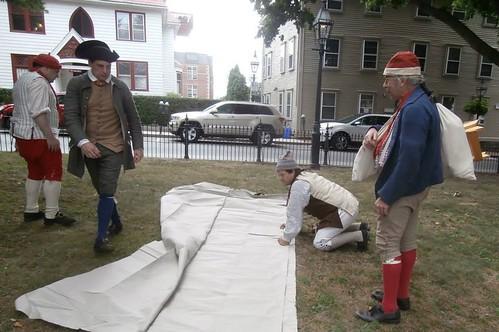 18th century sailors prepare to sew a sail