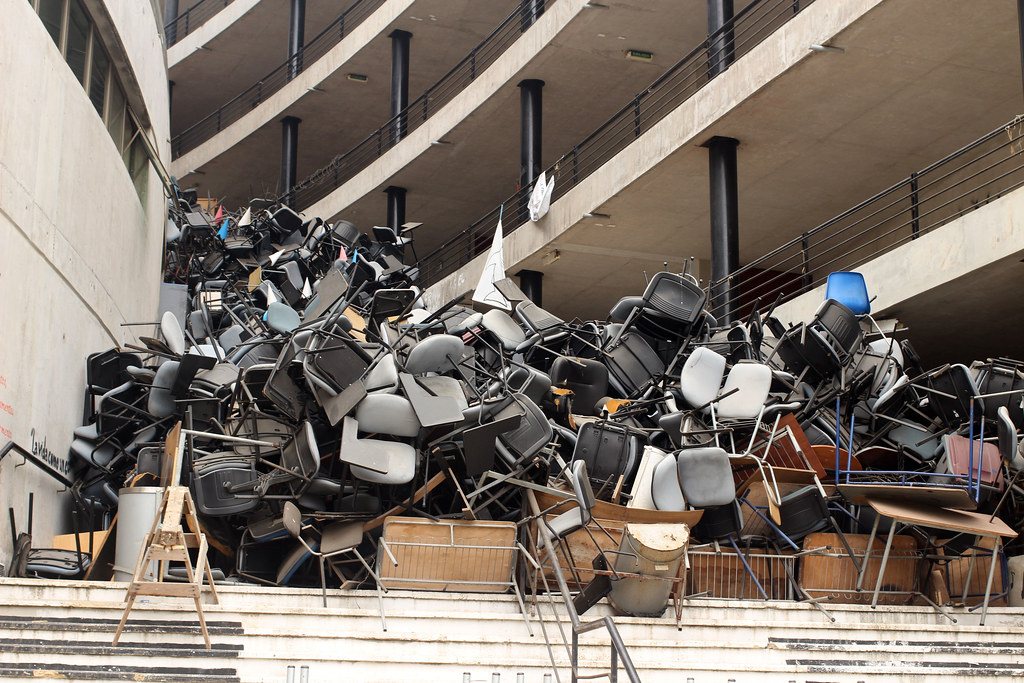 stacked chairs on the steps of an abandoned university