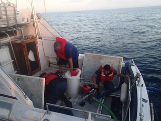 The crew of a 45-foot Response Boat from Coast Guard Station San Diego work to dewater a 30-foot pleasure boat off the coast of San Diego, Aug. 30, 2014. Mariners aboard the vessel PMS Escape II called the Coast Guard on channel 16, the international distress frequency, using a handheld radio at 5:58 p.m., to report their pleasure boat had lost propulsion, was taking on water, listing heavily on its port side and had no battery power to operate its bilge pumps or other electronics. (U.S. Coast Guard photo.)
