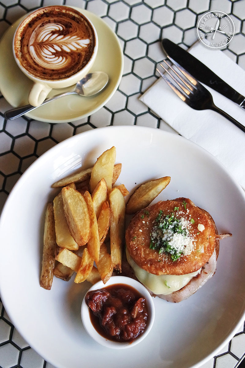 Elvis Burger with chips, and a cup of coffee, on a honey comb tiled table.