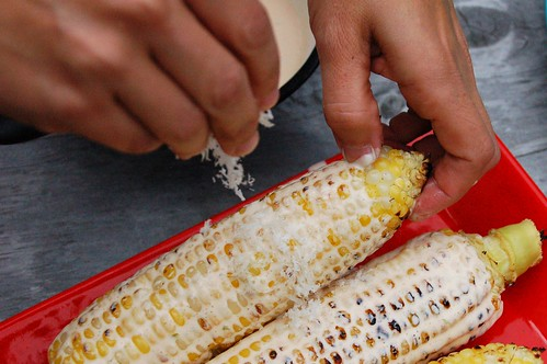 Sprinkling the corn ears with cheese by Eve Fox, The Garden of Eating, copyright 2014