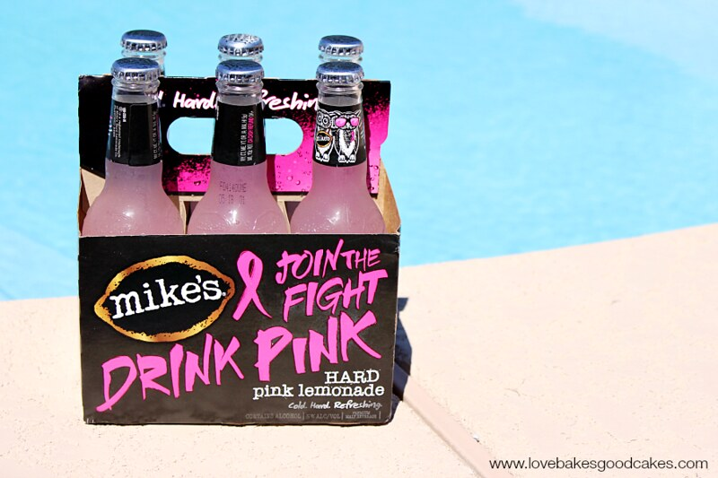 A case of Mike's Drink Pink Hard Lemonade sitting on a pool deck.