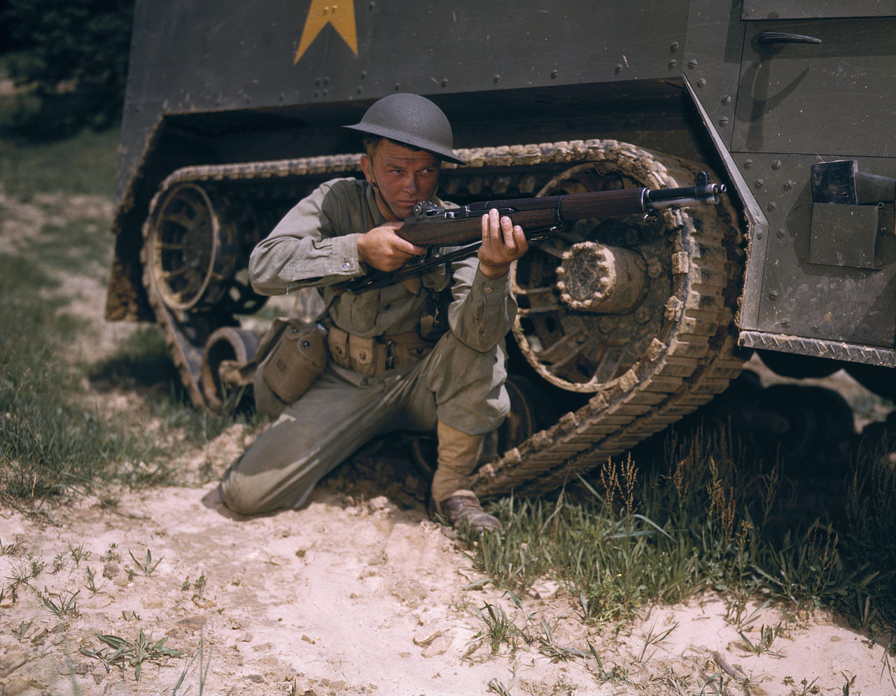A young soldier of the armored forces holds and sights his Garand rifle like an old timer, 1942