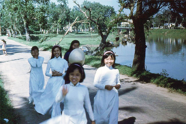 HUE 1963 - Smiling girls walk by canal