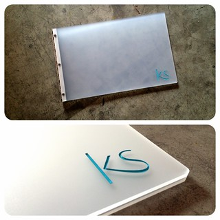 Custom graphic design portfolio book with engraved color fill treatment on frosted clear acrylic