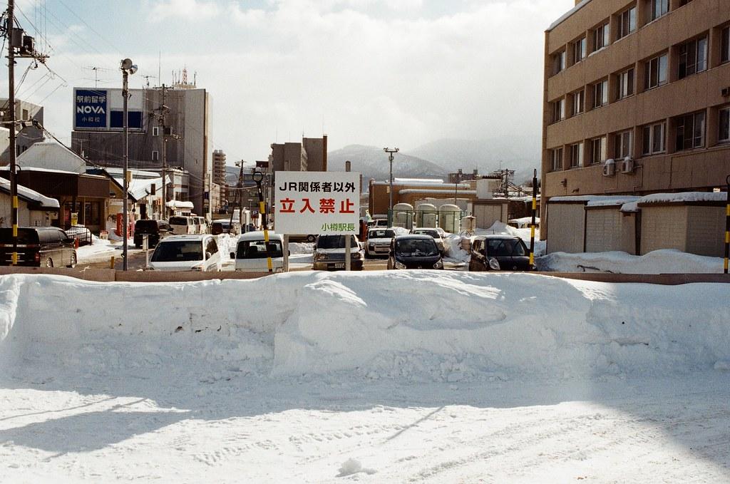 小樽 Otaru, Japan / Kodak ColorPlus / Nikon FM2 拍一下路邊的牌子,知道自己在哪裡。  路邊的雪被剷的方方塊塊的,但如果用手去摸,其實還是很綿密的。  Nikon FM2 Nikon AI AF Nikkor 35mm F/2D Kodak ColorPlus ISO200 8268-0031 2016/02/02 Photo by Toomore