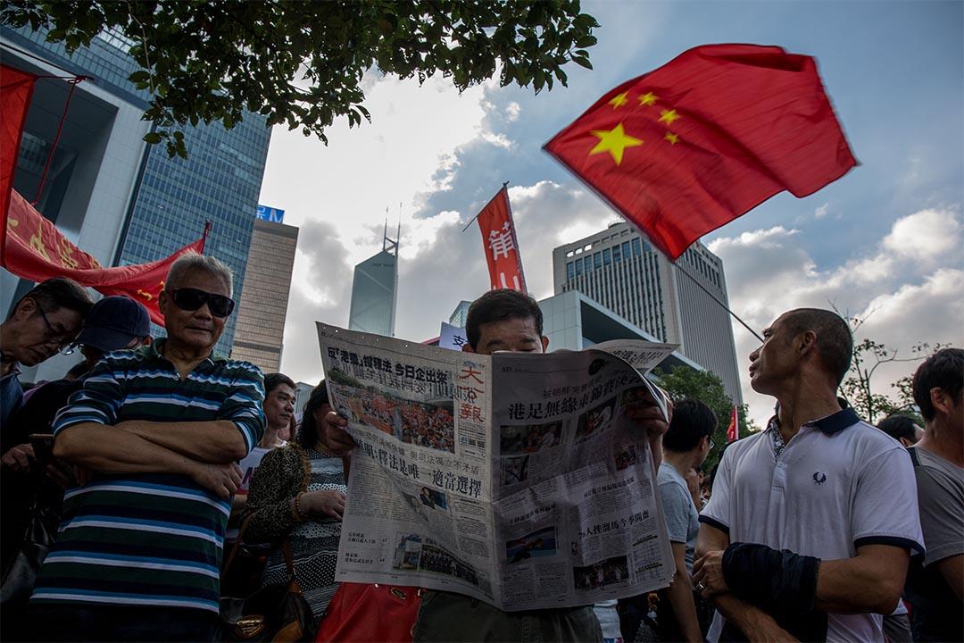2016年11月13日,金鐘,建制團體於添馬公園舉行支持人大釋法及反港獨集會,有參加者在集會上閱讀大公報。