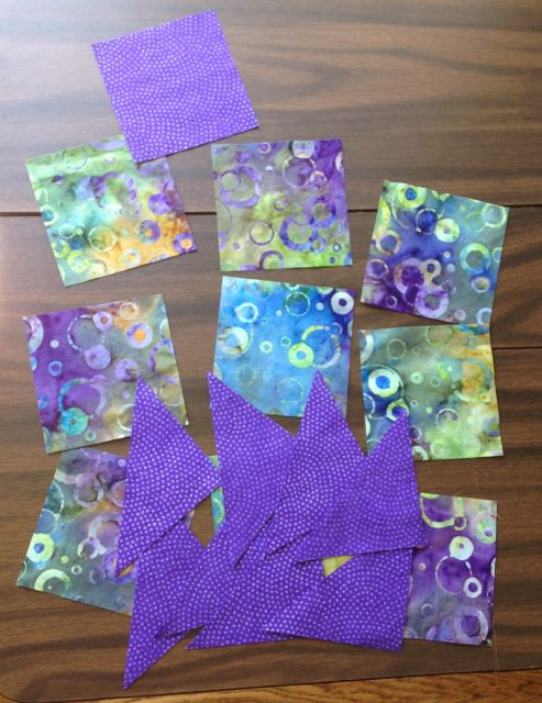 "I cut all my pieces. Nine 3.5"" squares of the background (one unused) and five 3.5"" squares of the star fabric, 4 of which were cut into HSTs."