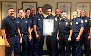 10 LAFD Firefighters standing in line looking forward, holding a certificate of appreciation.