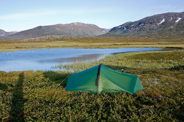 Lejr ved lille sø med udsigt mod Čaihnavárri