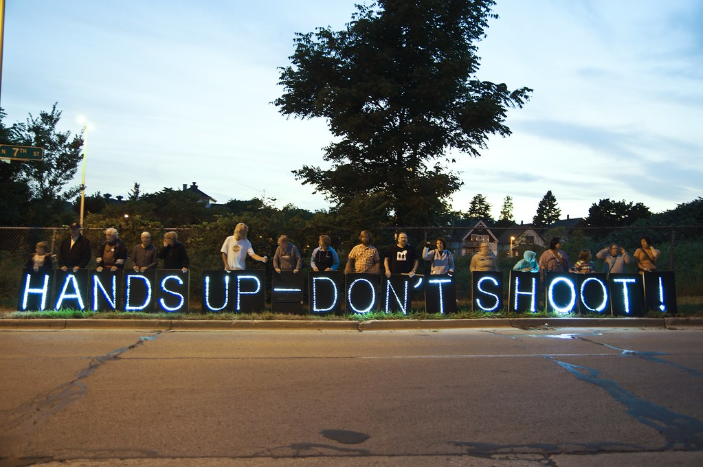 "A group of people hold signs that say ""hands up don't shoot"""