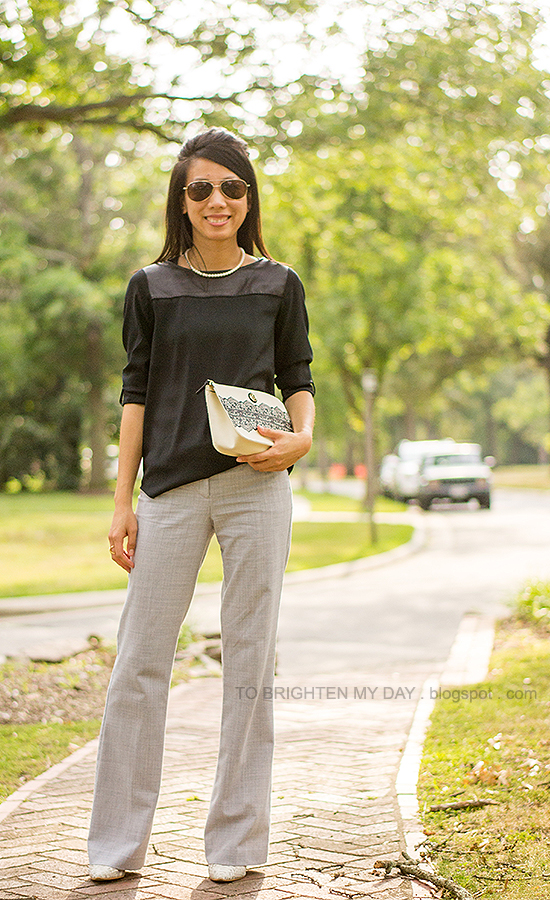 pearl necklace, black faux leather yoke top, gray trousers, lace printed clutch