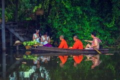 Buddhist Monk paddle on lakes to alms round by Wat…