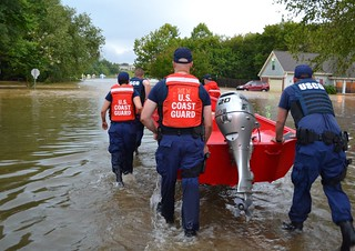 Flood response crewmembers push forward flat bottom boat in a flood in preparation for a rescue response Sept. 11, 2014. The Coast Guard responded to a flood in northern Mississippi rescuing several people and pets. (U.S. Coast Guard photo courtesy of Coast Guard Sector Lower Mississippi River)