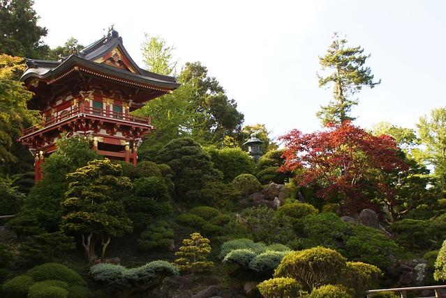 > Pagode du jardin japonais au milieu de buissons de différentes couleurs.
