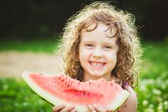Happy little girl eating watermelon in summer park…
