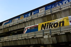 BTS Skytrain Central station with two trains completely plastered with advertising