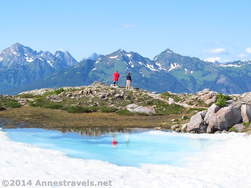 Hikers pause to enjoy the view near a frozen lake on Artist Ridge, Mount Baker-Snoqualmie National Forest, Washington