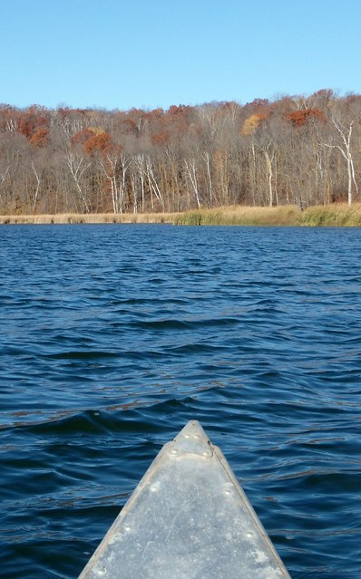 a canoe on a lake with brown oak trees in the background