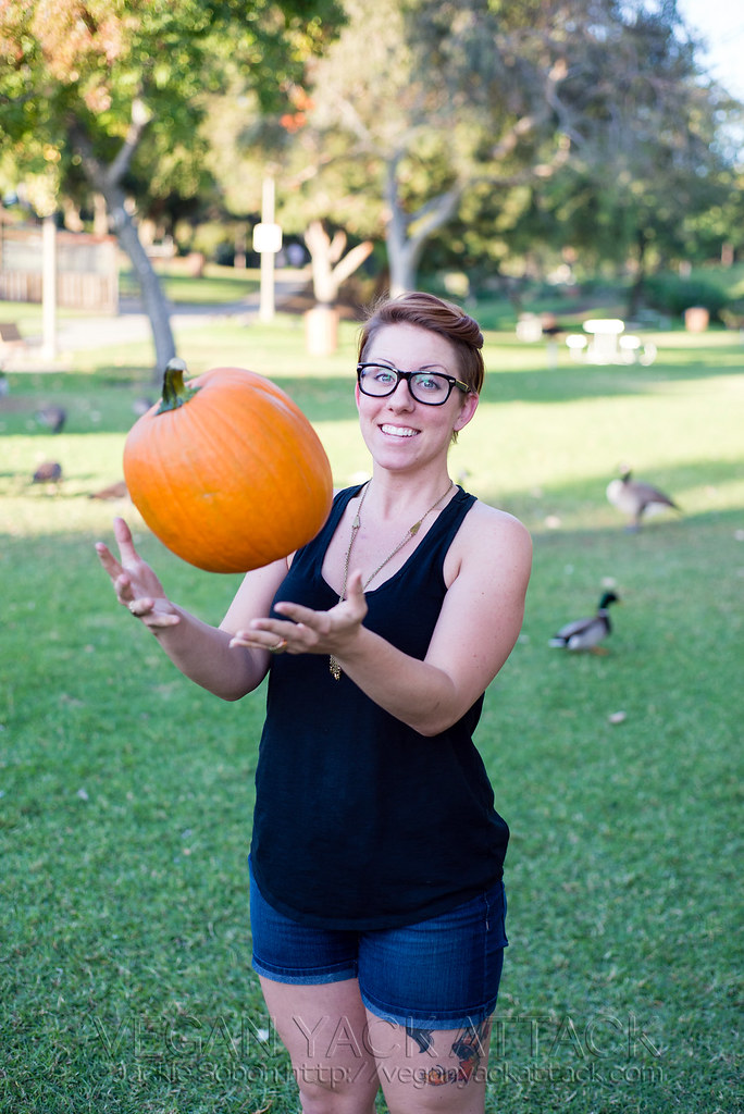Woman with short hair in a black tank top tossing a pumpkin into the air