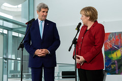 U.S. Secretary of State John Kerry listens to German Chancellor Angela Merkel speak as the two address the U.S. and German media before a bilateral meeting at the Chancellery in Berlin, Germany, on October 22, 2014. [State Department photo/ Public Domain]