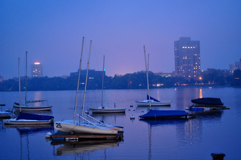 Foggy lake at dusk with sailboats