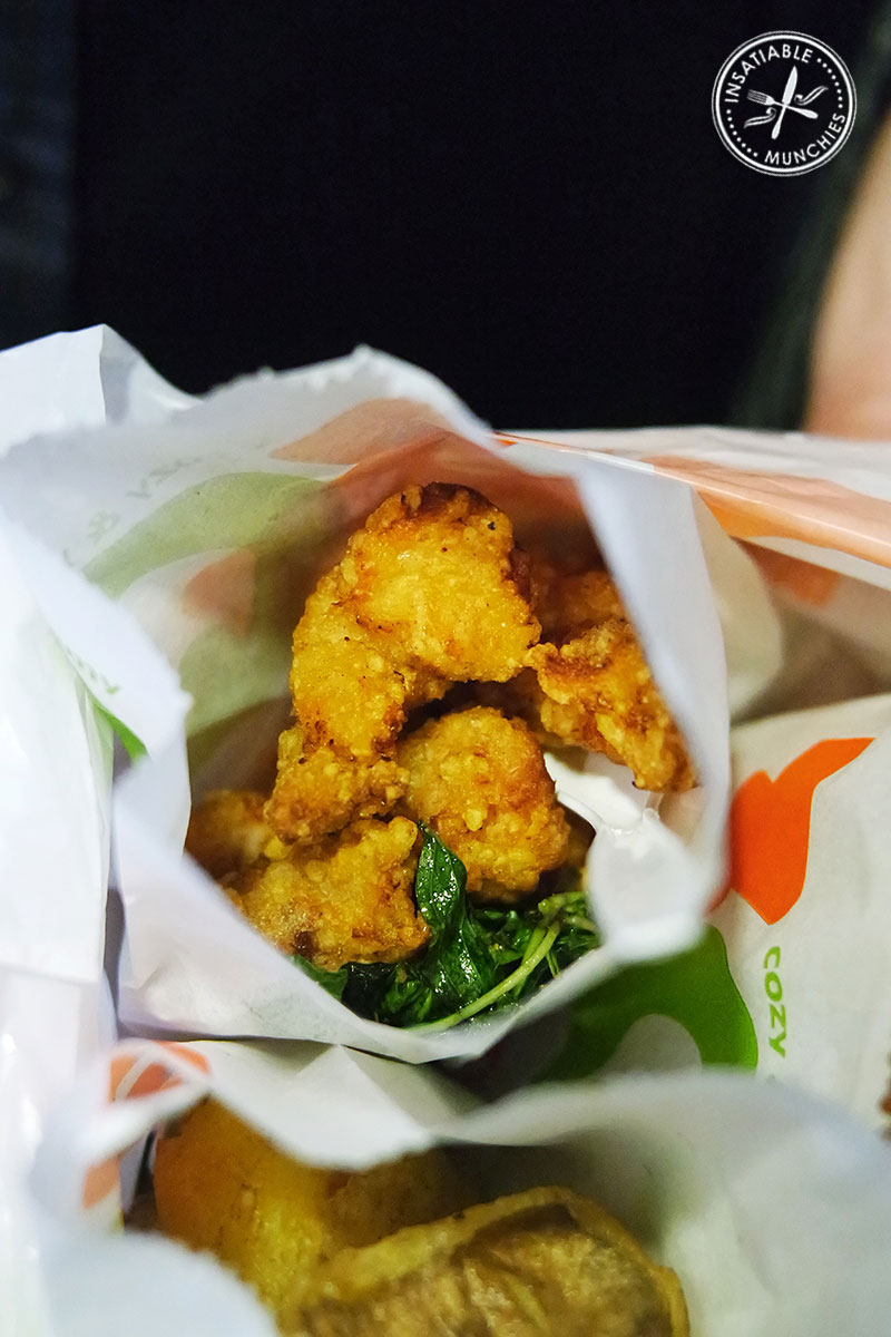 Pieces of Taiwanese Fried Chicken is seasoned with lots of pepper, and garnished with crispy fried herbs. Served in a paper bag.