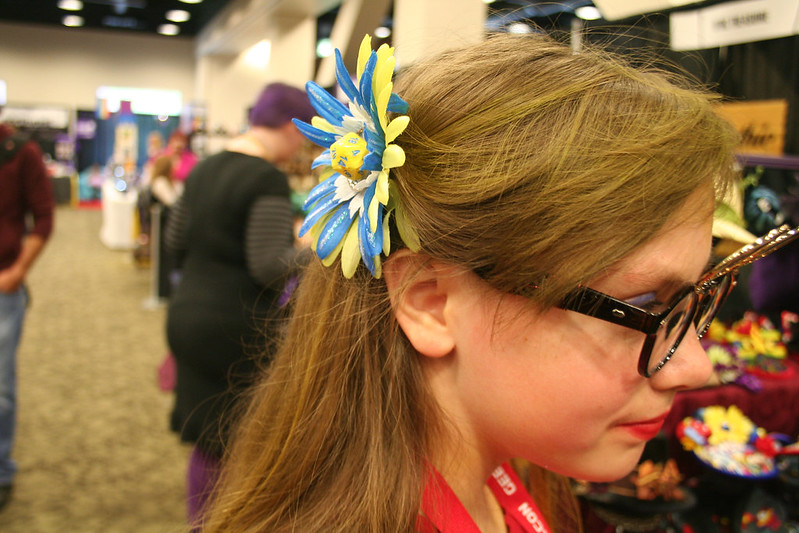 a girl wears a 12-sided die in her hair as a hairclip