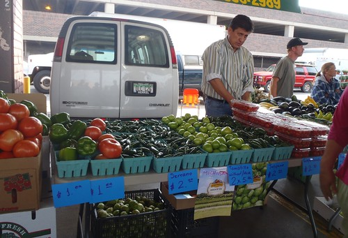 Board President Filiberto Villa Gomez, setting out produce at a farmers market, has been the driving force behind Farmers on the Move cooperative.