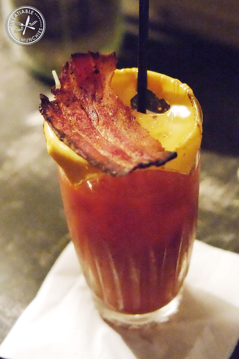 Mary's take on a bloody mary: Cheese is melted onto the top of a glass of bloody mary, and topped with a piece of crispy bacon.