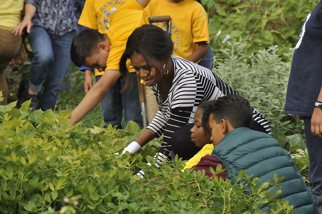 Michelle Obama harvests from the White House garden alongside three students.