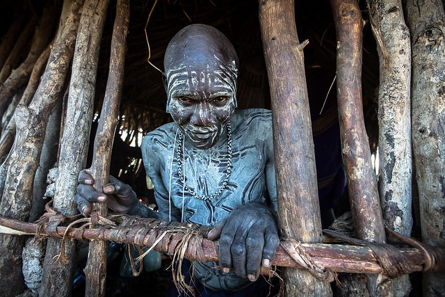Mursi tribe warrior waking inside the hut