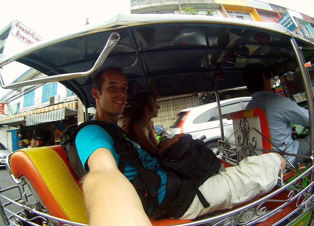 Tuktuk a toda mecha y se nos ve de lado montados por Bangkok con todas las mochilas encima