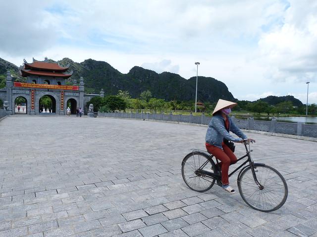 Mujer vietnamita montando en bici en Hoa Lu (Vietnam)