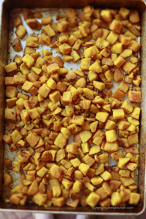 Cubes of roasted pumpkin in a large sheet pan.