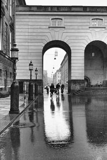 Image of Christiansborg Palace near Copenhagen. shadow people rain bicycle port reflections copenhagen square denmark 50mm cyclist københavn lampposts sonnar carlzeiss slotsholmen zm wetreflection bicyclerider csonnart1550 rigsdagsgården zeiss50mmf15csonnarzm