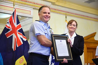 Cmdr. Mark Driver, Operation Bahamas, Turks and Caicos director, accepts the Joint Operations Interdiction award from Marilyn Quagliotti in New Providence, Bahamas, Nov. 13, 2014.OBAT is a multi-agency, international drug interdiction effort focused primarily on stemming the flow of illicit drugs from South America and the Caribbean to the Bahamas, the Turks and Caicos Islands, and the United States. U.S. Coast Guard photo.