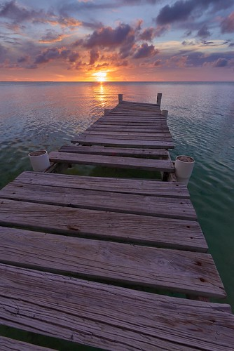 wood travel blue sunset red sea sky orange white black water yellow clouds pier boat waves belize gray violet su centralamerica cayecaulker